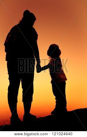 Silhouette Back View Of Mother And Daughter Clasping Hand Together At Sunset.
