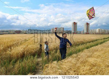 Children run the kite in a wheat field