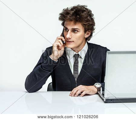 Businessman talking by cell phone while working with PC computer.