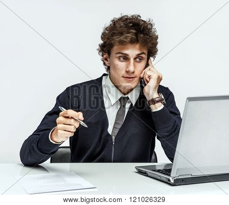 Successful businessman going to make a call by cell phone while working with PC computer.