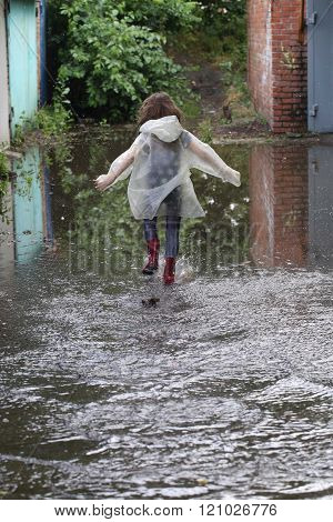 Girl In Rubber Boots Running Through A Puddle
