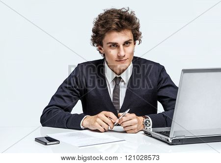 Serious businessman with arms across at the workplace in the office