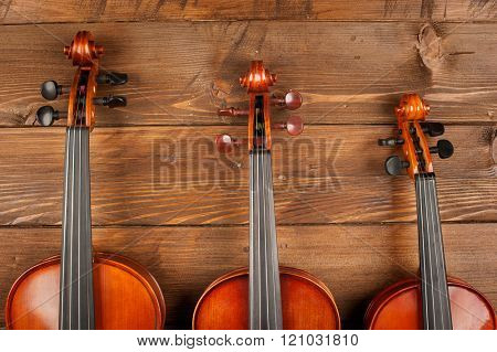 three violins in wood background