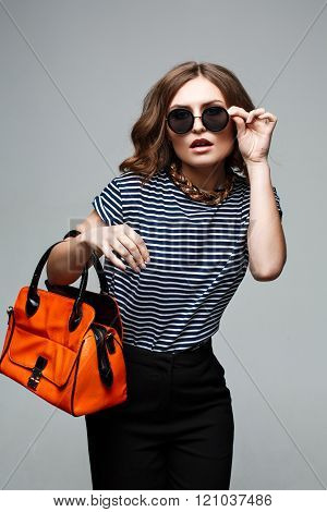 woman hands holding orange bag.