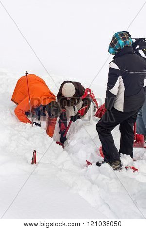 WERTACHER HOERNLE, WERTACH, GERMANY - FEBUARY 28 2016: Team of Alpine search and rescue rescuers training to locate and rescue a person buried off-piste in snow digging below the surface with spades