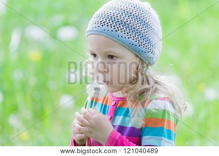 Little blonde girl wearing striped knitted hat blowing on white puffy dandelion seed head at her han