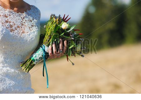 Bouquet in hands of bride. Wedding mountains.