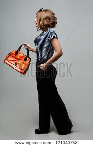The young fashion girl standing in trendy clothes leather boots with an orange bag