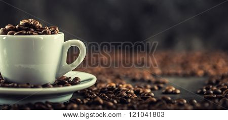 Coffee beans. Coffee cup full of coffee beans. Toned image