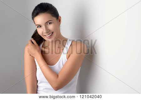 Woman In Sleeveless Blouse Adjusting Hair