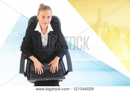 Businesswoman sitting on swivel chair with laptop against cityscape