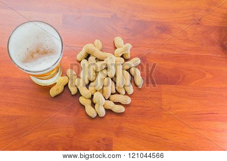 glass of lager beer and unpeeled peanuts on the table