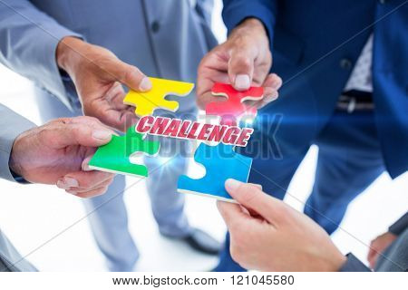 The word challenge against business colleagues holding piece of puzzle