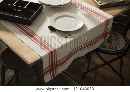 Tablecloth With Printed Red Stripes Laid On Table With Dinnerware