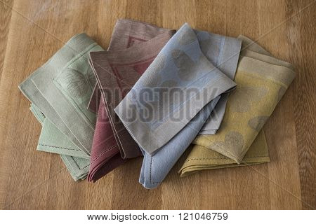 Folded Placemats And Napkins Of Various Colors On Wooden Surface