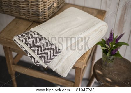 Folded White Towel With Black Herringbone Design On Square Sidetable