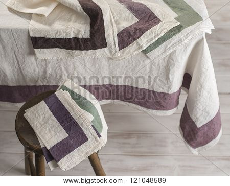 Bordered Off-white Tablecloth And Folded Napkins