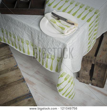 Dinnerware On Table Covered In White Fork-patterned Linen