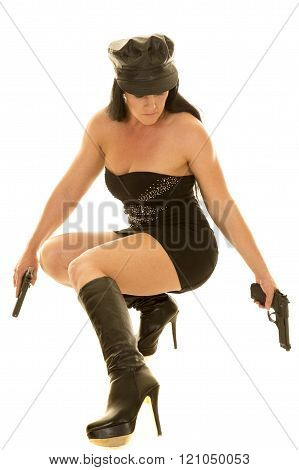 a woman crouched down in her little black dress holding on to pistols.