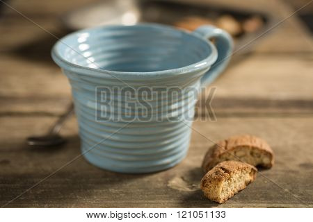 Empty Blue Teacup Between Spoon And Biscuits