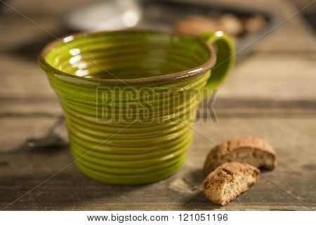 Empty Green Teacup Between Spoon And Biscuits