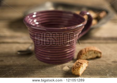 Empty Brown Teacup, Framed At Center, Between Spoon And Biscuits