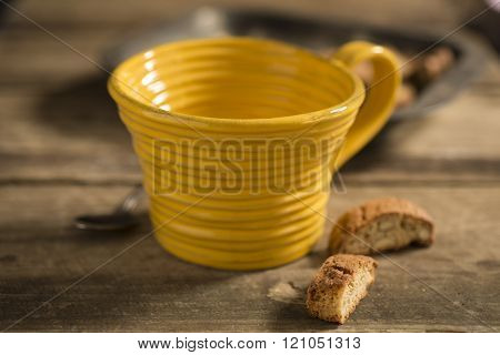 Empty Yellow Teacup, Framed At Center, Between Spoon And Biscuits