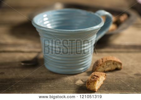 Empty Blue Teacup, Framed At Center, Between Spoon And Biscuits