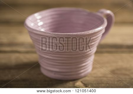 Close Up Of Pink Teacup On A Wooden Surface