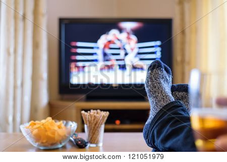 Television, TV watching (boxing match) with snacks and alcohol lying on table