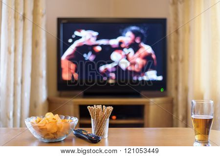 Television, Tv Watching (boxing Match) With Snacks And Alcohol Lying On Table - Stock Photo