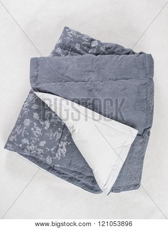 Dark Gray Duvet With White Underside Exposed Over White Backdrop