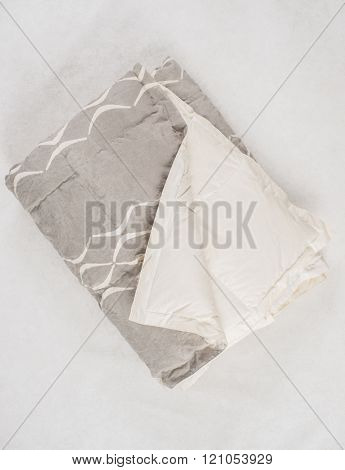 A Folded Gray Duvet With White Concave Line Pattern