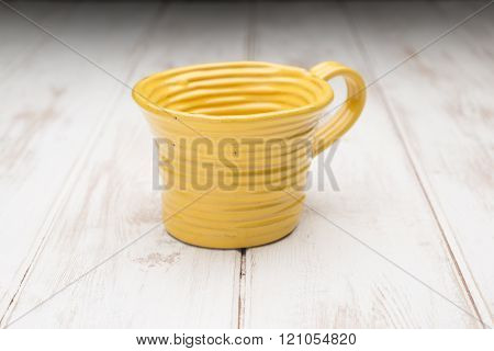 Yellow Teacup On A White Wooden Panel Surface