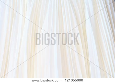 Background of white pleated fabric. Fabric gentle background.