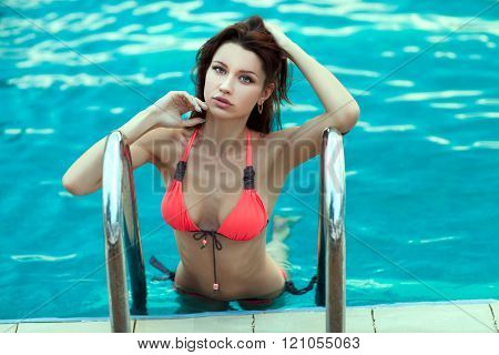 Woman In A Swimsuit Posing Swimming Pool.