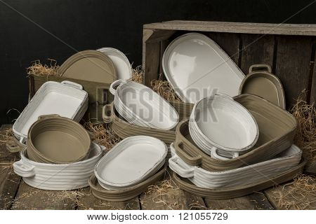 A Collection Of White And Tan-colored Earthenware With Dried Grass