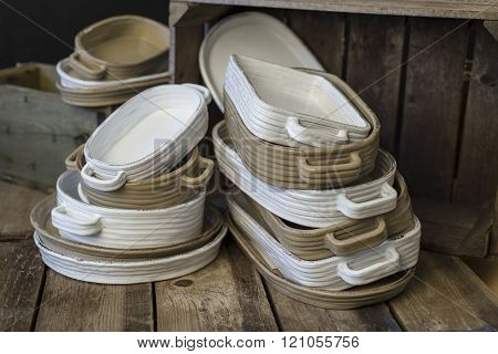 Stacks Of White And Tan-colored Earthenware With Handles Facing About