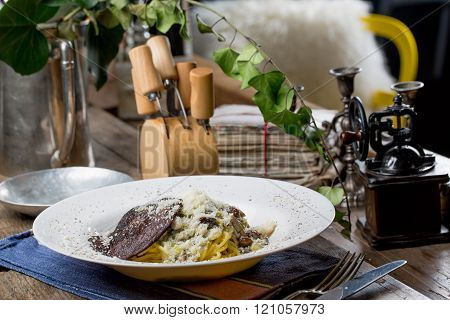 Tasty spagetti with honey fungus and shiitake mushrooms on an old wooden table