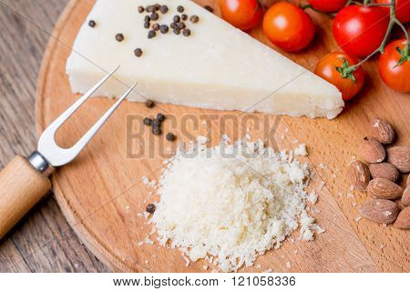 Grated pecorino cheese on wooden cutting board with tomatoes selective focus