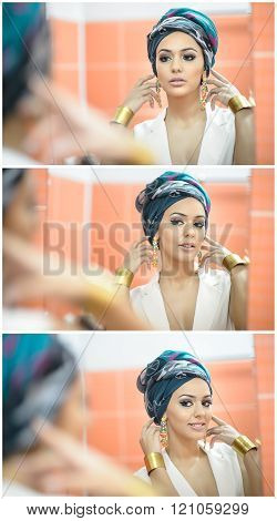 Young beautiful woman with turban and golden accessories looking into large mirror. Seductive lady with earrings posing, mirror reflection photo. Elegant girl in white smiling posing into mirror
