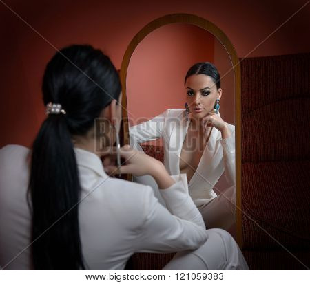 Young beautiful brunette woman in elegant white suit with trousers looking into large mirror. Seductive dark hair girl posing, studio shot.Elegant lady in white suit with jacket with plunging neckline