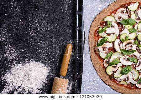 Pizza with vegetables on baking tray, flour and rilling pin on rustic background. Top view.
