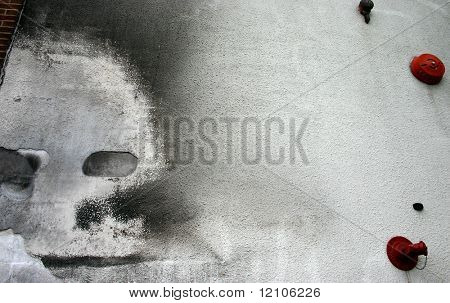 a face seems to appear on a weather stucco wall with fire alarms and sprinkler