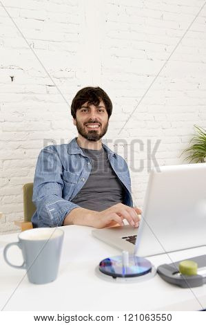 corporate portrait of young hispanic attractive hipster businessman on his 30s working at modern home office with computer laptop looking happy and satisfied in creative freelancer success