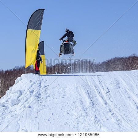 Snowmobile on the route in a jump in air in Kamchatka