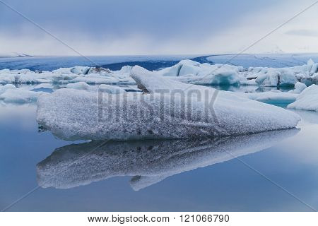 A stand alone luminous Blue Icebergs Floating In Jökulsárlón Glacial Lagoon, in the background other ice shapes and the mountain, Iceland