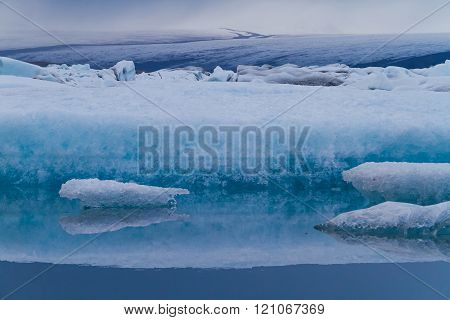 Abstract image of Luminous Blue Icebergs Floating In Jökulsárlón Glacial Lagoon, with mountains in the background, Iceland