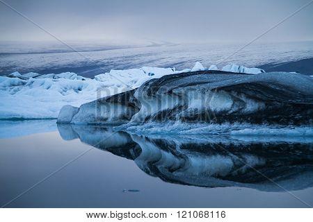 Luminous blue and black icebergs floating in Jokulsarlon glacial lagoon Iceland