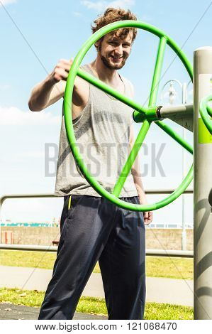 Active Man Exercising With Tai Chi Wheel.